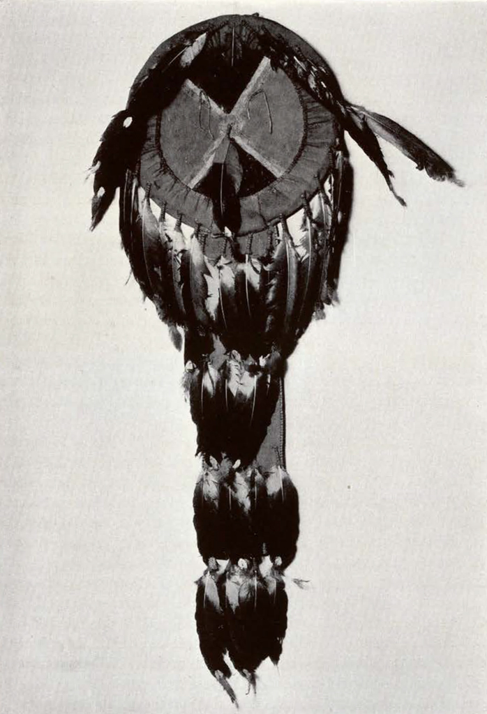 a round shield with feathers around the rim and a tail with three layers of feathers, rim feathers parted to show circle divided into four equal parts