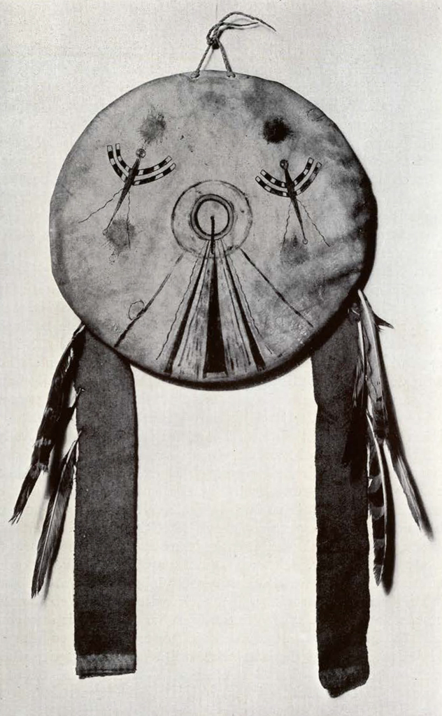 round shield with two long pieces and feathers dangling from the sides, concentric circles in the middle of the shield and two dragonflies on either side