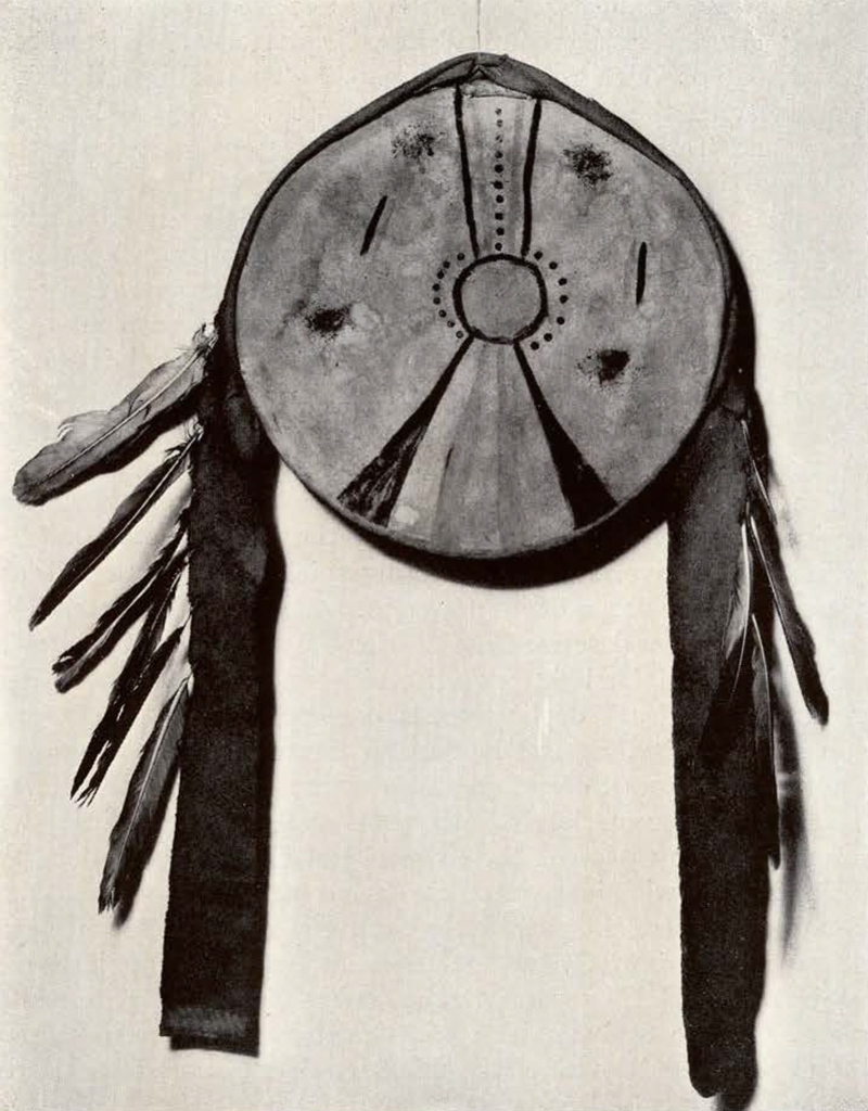 round shield with two long pieces and feathers dangling from the sides, a circle in the middle with radiating lines