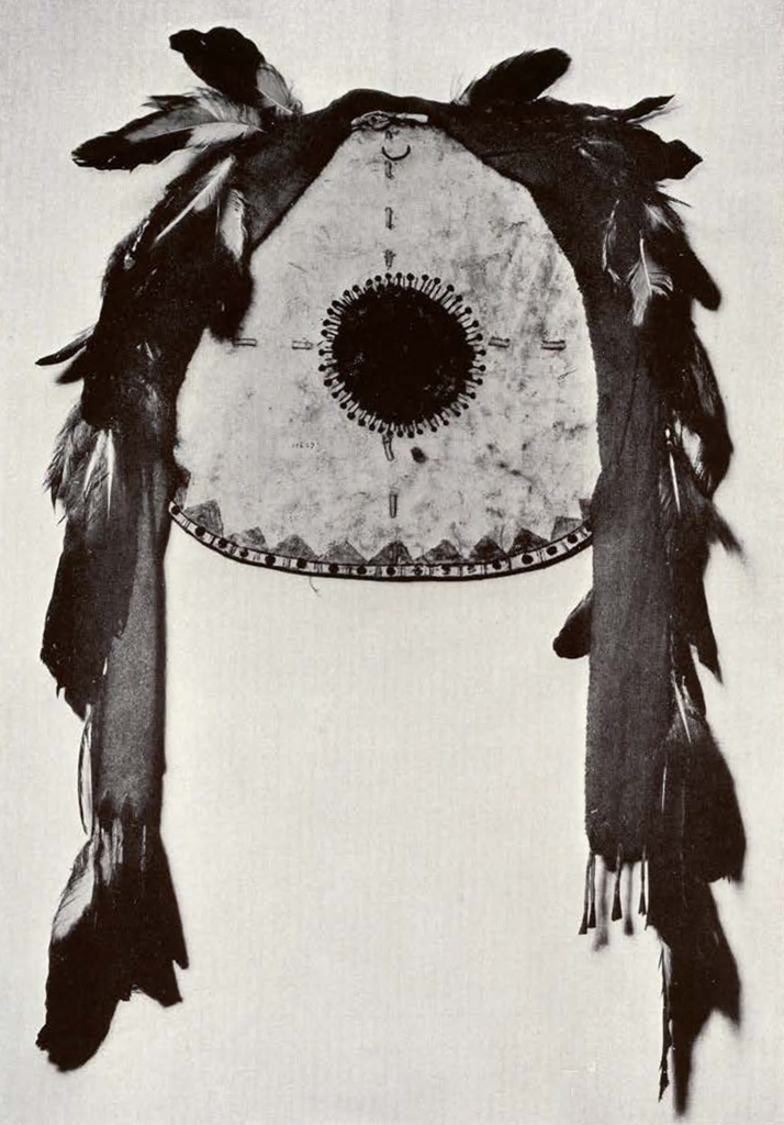 round shield with feathers and two long strips hanging from the side, circle in the middle with small radiating lines