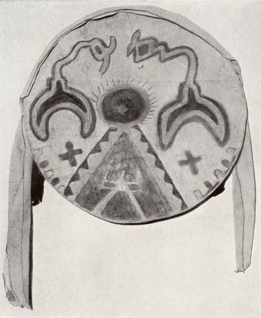 round shield with a circle sitting atop a triangle, and two crescent moon shapes with zigzagging tails