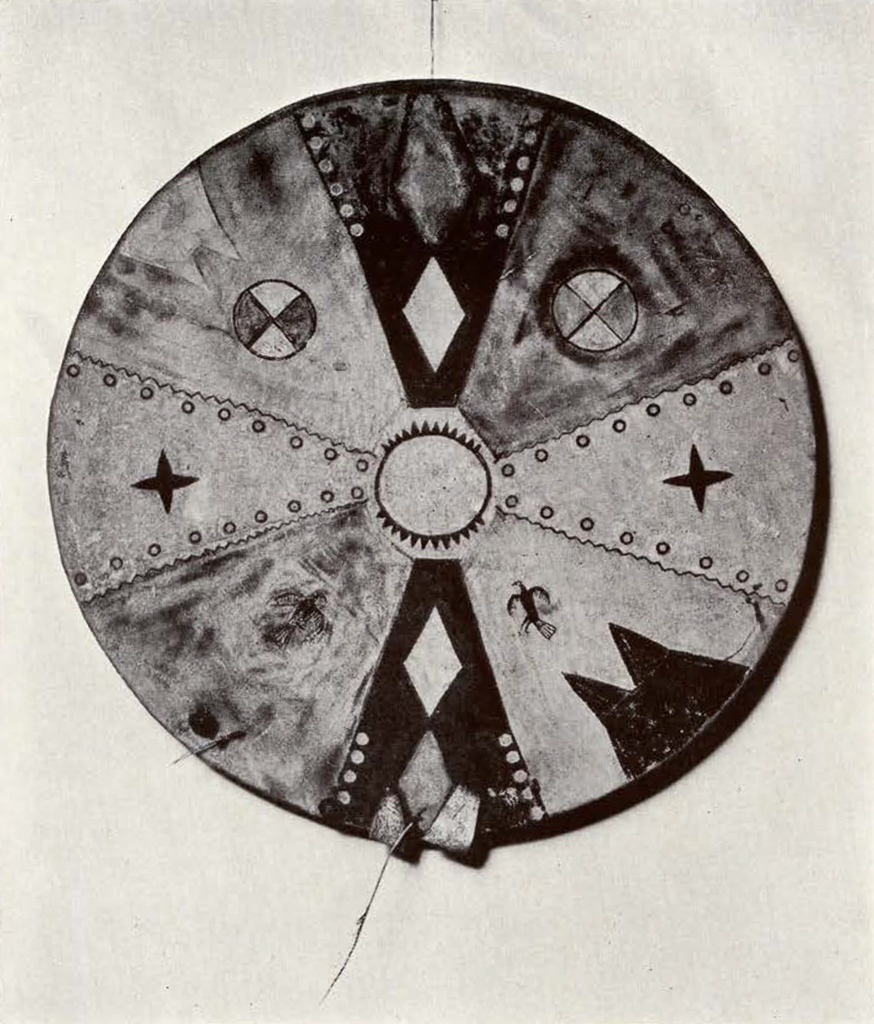 round shield separated into eighths, with a circle in the middle and different motifs in the 8 sections