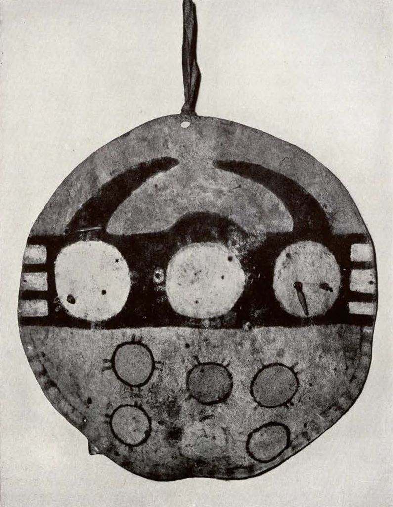 round shield with six circles in two rows on the bottom half , three larger circles above, and two horns