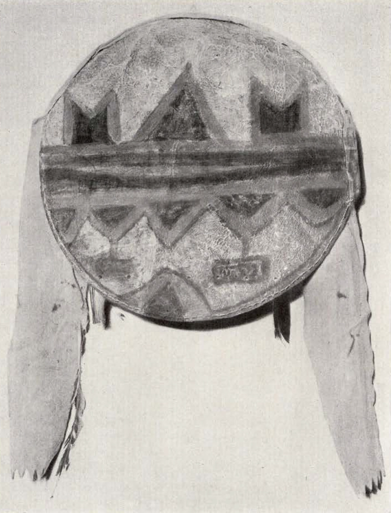 round shield with two long pieces hanging of the sides, a stripe in the middle and triangles on either side