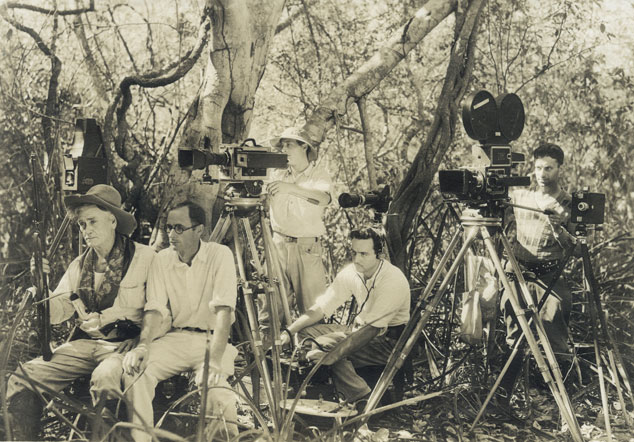 A staged photograph of the crew: Left to right:  George Rawls (actor), David Crosby (camera and director) in front of Debrie Parvo  silent movie camera, operated by Arthur Rossi (2nd camera),  Ainslee Davis sitting low with mixer, (unidentified crewman) with Mitchell synch sound camera.